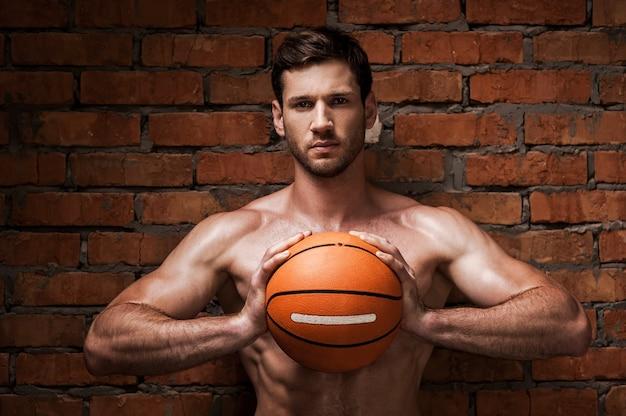 Ben je klaar om te spelen? zelfverzekerde jonge gespierde man met basketbalbal