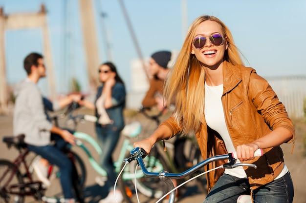 Ben je klaar om wat plezier te hebben? mooie jonge glimlachende vrouw die op haar fiets leunt en naar de camera kijkt terwijl haar vrienden op de achtergrond praten