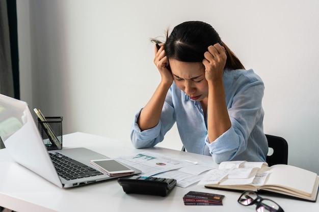 Benadrukt aziatische vrouw die op haar werkplek werkt. bedrijfsconcept. detailopname