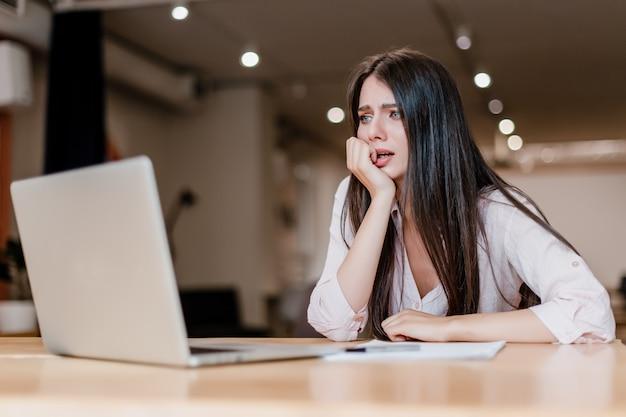Benadrukt, bang en verward vrouw met behulp van laptop op kantoor