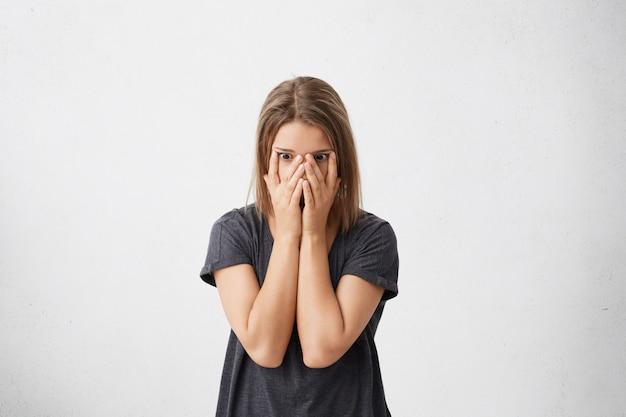 Benadrukt bang vrouw in casual t-shirt voor haar gezicht, bang gevoel