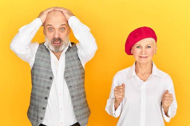 Benadrukt bejaarde man met baard hand in hand op het hoofd en staren naar de camera met volledig ongeloof, in paniek raken, zijn vrouw probeert hem te steunen