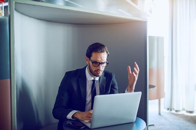 Benadrukt blanke bebaarde zakenman als pak zittend op de werkplek, met behulp van laptop en proberen op tijd te rapporteren.
