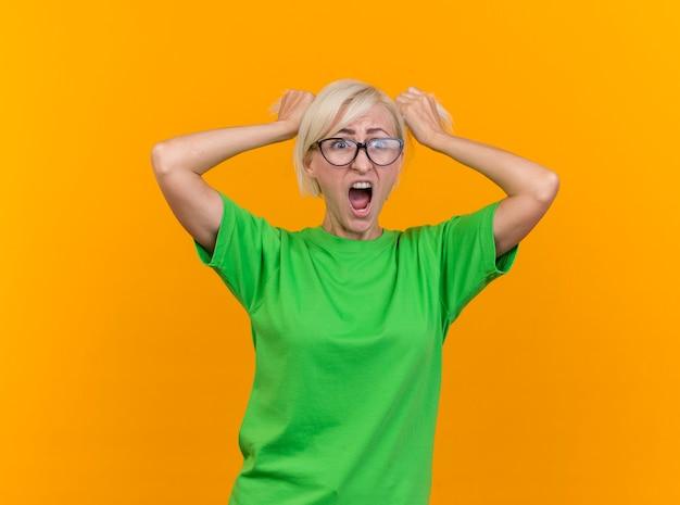 Benadrukt blonde slavische vrouw van middelbare leeftijd die glazen draagt die kant bekijkt die haar trekt en schreeuwt geïsoleerd op gele achtergrond