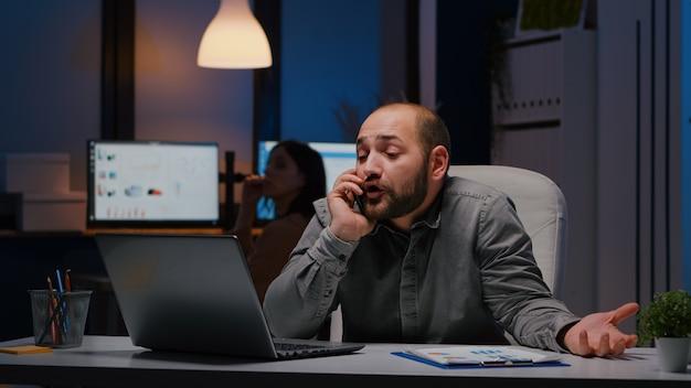 Benadrukt boze zakenman zittend aan bureau tafel bespreken bedrijfsprobleem