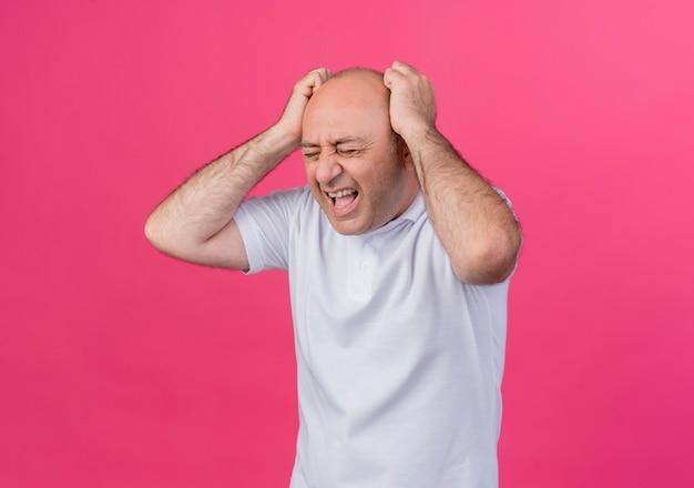 Benadrukt casual volwassen zakenman handen zetten hoofd schreeuwen met gesloten ogen geïsoleerd op roze achtergrond met kopie ruimte