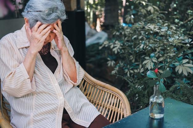 Benadrukt depressief vermoeid triest boos aziatische oude aziatische bejaarde senior oudere vrouw zittend in de tuin.