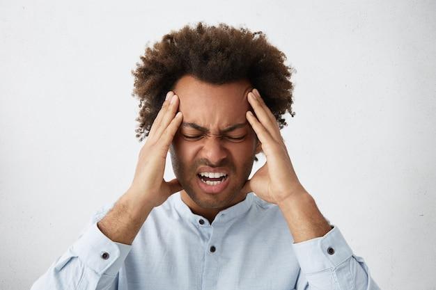 Benadrukt gemengd ras man met hoofd van krullend haar fronsend zijn gezicht hand in hand op hoofd
