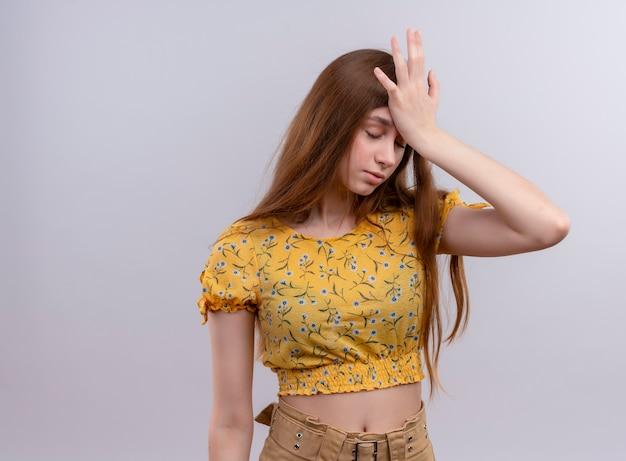 Benadrukt jong meisje hand op het hoofd zetten op geïsoleerde witte muur met kopie ruimte
