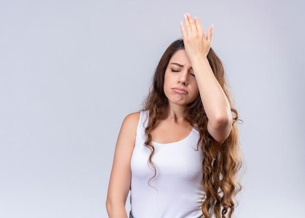 Benadrukt jong mooi meisje hand op het hoofd zetten met gesloten ogen op geïsoleerde witte muur met kopie ruimte