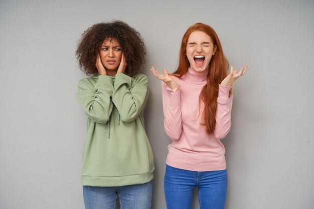Benadrukt jonge aantrekkelijke dames in vrijetijdskleding die hun wenkbrauwen fronsen en negatieve emoties uitdrukken terwijl ze poseren over de grijze muur, een slechte dag hebben