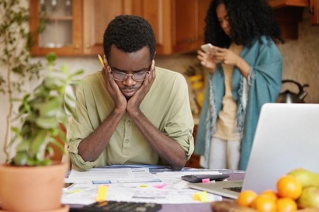 Benadrukt jonge afrikaanse man doet papierwerk thuis, hand in hand op het hoofd