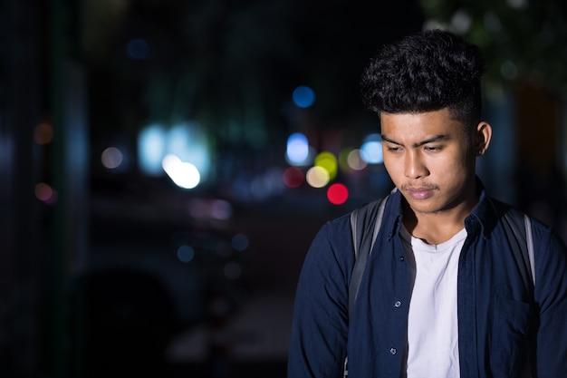 Benadrukt jonge aziatische man denken terwijl neerkijkt in de straat van de stad 's nachts