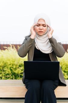 Benadrukt jonge aziatische moslimvrouw in groene pak en werken op een computer in het park