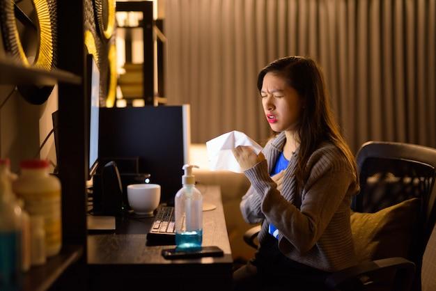 Benadrukt jonge aziatische vrouw die ziek wordt terwijl ze 's avonds laat vanuit huis werkt