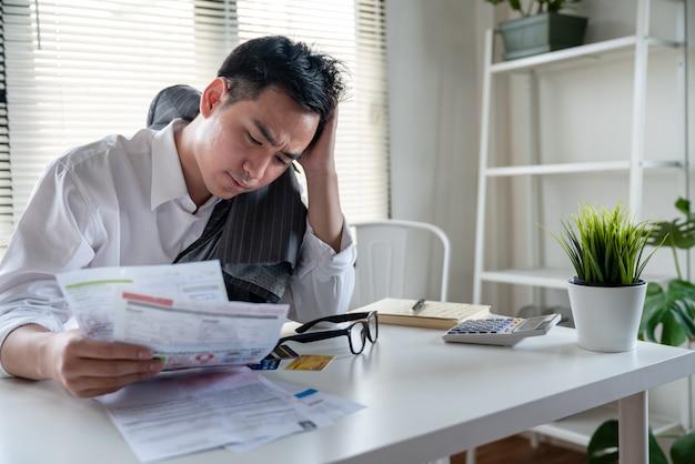 Benadrukt jonge aziatische zakenman die zoveel onkostenrekeningen zoals elektriciteitsrekening, waterrekening, internetrekening, mobiele telefoonrekening en creditcardrekening in zijn hand houdt, geen geld om schulden te betalen