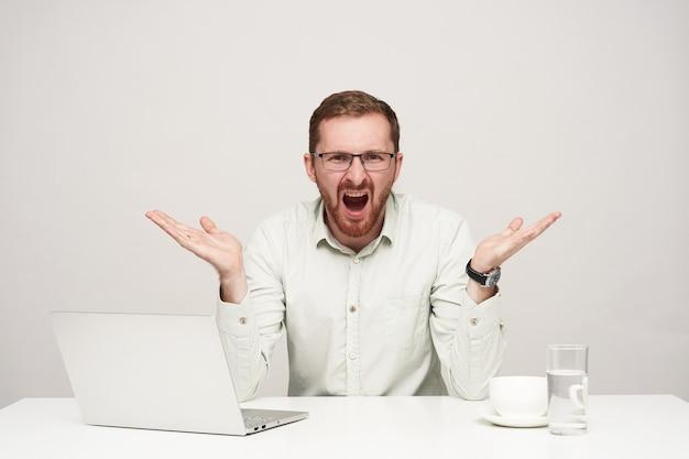 Benadrukt jonge bebaarde blonde man in glazen emotioneel zijn handpalmen verhogen terwijl schreeuwen met brede mond geopend, geïsoleerd op witte achtergrond