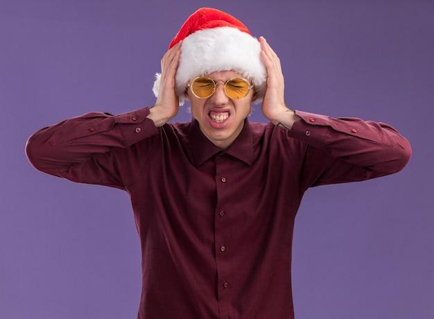 Benadrukt jonge blonde man met kerstmuts en bril handen op het hoofd houden met strak gesloten ogen geïsoleerd op paarse muur
