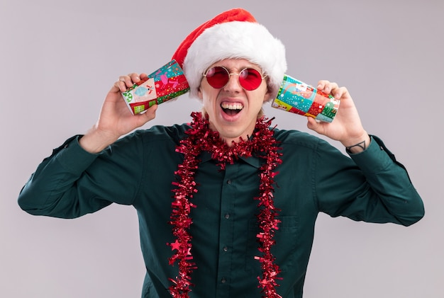Benadrukt jonge blonde man met kerstmuts en bril met klatergoud slinger rond nek met plastic kerstbekers naast oren luisteren naar geheimen