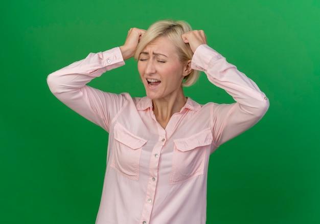 Benadrukt jonge blonde slavische vrouw hoofd met vuisten aan te raken met gesloten ogen geïsoleerd op groene achtergrond