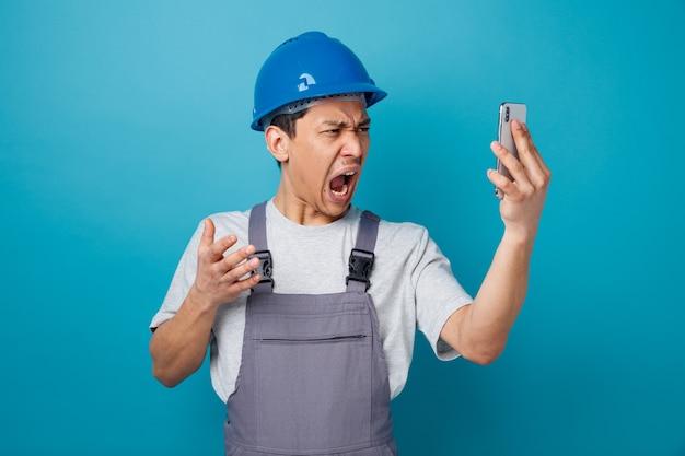 Benadrukt jonge bouwvakker dragen veiligheidshelm en uniform bedrijf en kijken naar mobiele telefoon schreeuwen hand in de lucht houden
