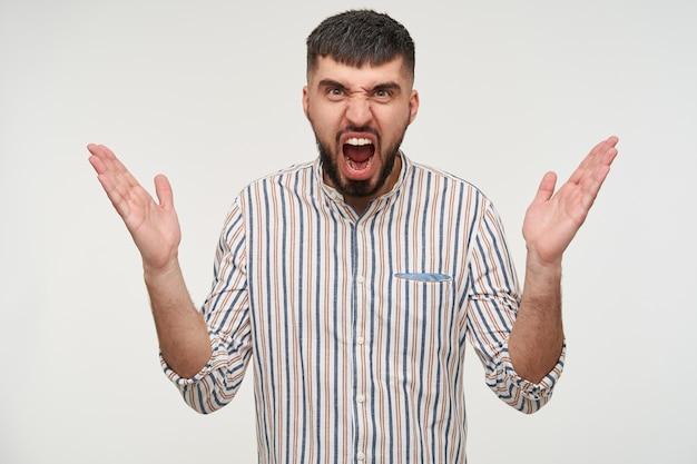 Benadrukt jonge bruinogige brunette bebaarde man die emotioneel zijn handen en fronsend gezicht opheft terwijl hij boos schreeuwt, staande tegen een witte muur