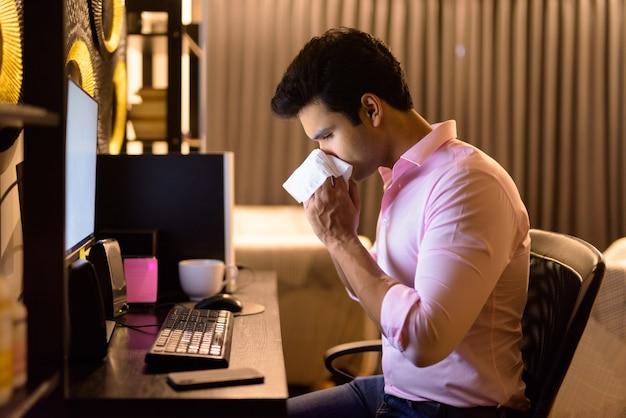 Benadrukt jonge indiase zakenman ziek worden terwijl hij 's avonds laat thuis overuren maakt