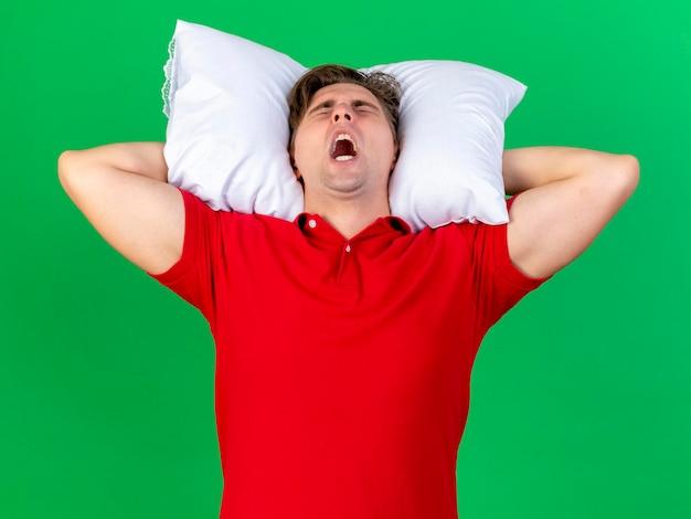 Benadrukt jonge knappe blonde zieke man met kussen onder het hoofd schreeuwen met gesloten ogen geïsoleerd op groene muur