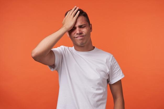 Benadrukt jonge kortharige brunette man die zijn ogen gesloten houdt terwijl hij zijn wenkbrauwen fronst en de handpalm op het voorhoofd houdt, geïsoleerd over oranje achtergrond