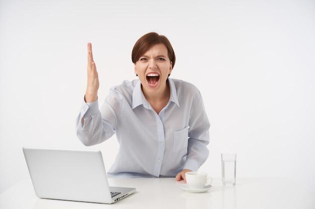Benadrukt jonge kortharige brunette vrouw met casual kapsel boos schreeuwen en emotioneel haar hand verhogen, gekleed in blauw shirt terwijl poseren op wit