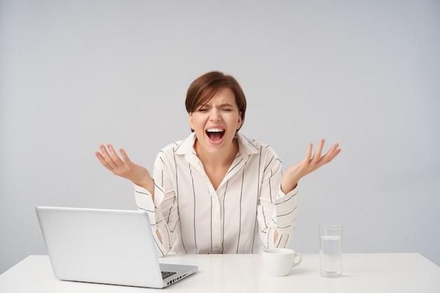 Benadrukt jonge kortharige brunette vrouw met natuurlijke make-up haar ogen gesloten houden terwijl verhit schreeuwen met opgeheven handen, gestreept shirt dragen op wit