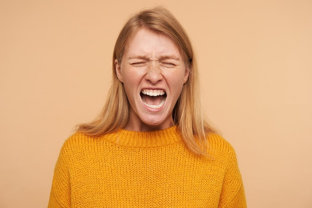 Benadrukt jonge langharige roodharige vrouw met casual kapsel die haar ogen gesloten houdt terwijl ze haar gezicht dwars grimassen, geïsoleerd op beige