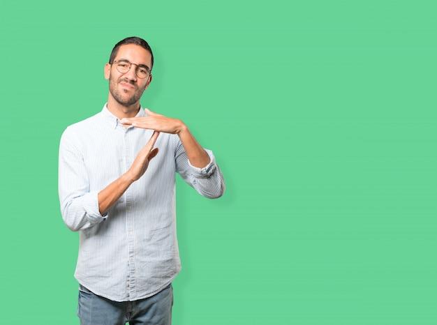 Benadrukt jonge man die een time-out gebaar met zijn handen