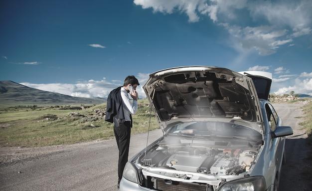 Benadrukt jonge man met kapotte auto