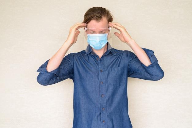 Benadrukt jonge man met masker en gezichtsscherm met hoofdpijn op betonnen muur