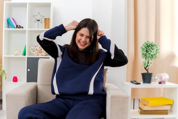 Benadrukt jonge mooie kaukasische vrouw zittend op een stoel in ontworpen woonkamer hoofd met vuisten met gesloten ogen aan te raken