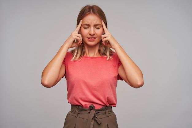 Benadrukt jonge mooie vrouw met kort blond haar, gekleed in roze t-shirt, houdt de ogen gesloten en probeert zich te concentreren, met wijsvingers op haar slapen terwijl ze op een witte achtergrond staat