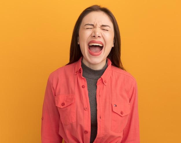 Benadrukt jonge mooie vrouw schreeuwen met gesloten ogen geïsoleerd op oranje muur