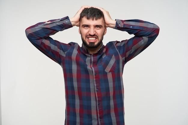 Benadrukt jonge vrij kortharige brunette man met baard zijn hoofd geklemd met opgeheven handen en fronsend gezicht tijdens het kijken, geïsoleerd over witte muur