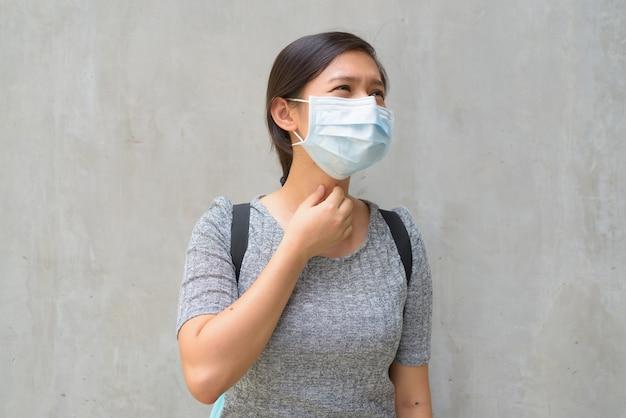 Benadrukt jonge vrouw die met masker ziek kijkt en buiten keelpijn heeft