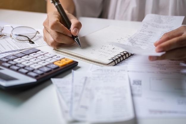Benadrukt jonge vrouw rekeningen, belastingen, bankrekening saldo en het berekenen van uitgaven in de woonkamer thuis te controleren