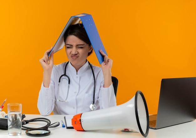 Benadrukt jonge vrouwelijke arts die medische mantel en stethoscoop draagt ?? die aan bureau zit met spreker van medische hulpmiddelen en laptop die map op hoofd met gesloten ogen houdt die op gele muur wordt geïsoleerd