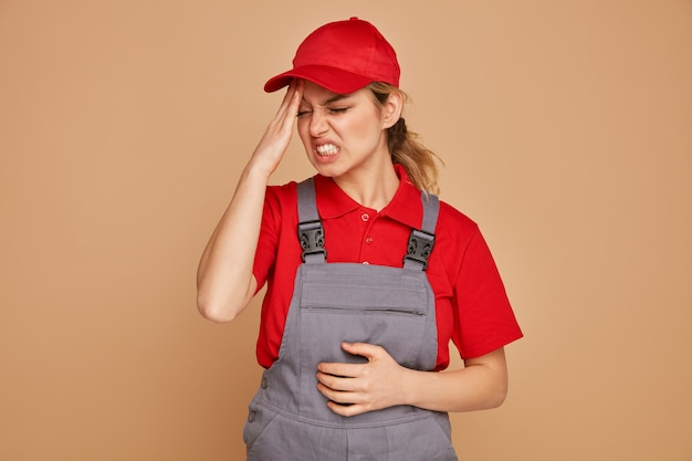 Benadrukt jonge vrouwelijke bouwvakker die eenvormig en glb draagt die hand op hoofd met gesloten ogen houdt