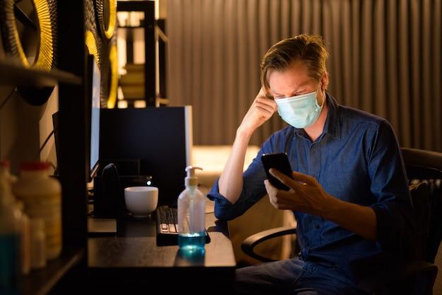Benadrukt jonge zakenman met masker met behulp van telefoon tijdens het werken vanuit huis 's avonds laat