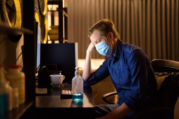 Benadrukt jonge zakenman met masker op zoek moe tijdens het werken vanuit huis 's avonds laat