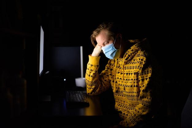 Benadrukt jongeman met masker op zoek moe tijdens het werken vanuit huis 's avonds laat in het donker