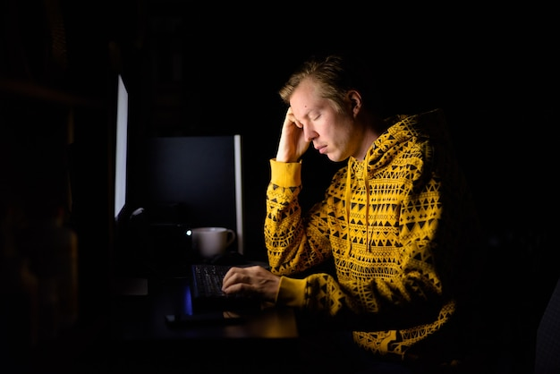 Benadrukt jongeman op zoek moe tijdens overuren thuis in het donker