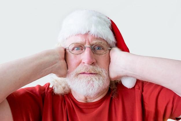 Benadrukt man in santa hat oren met handen sluiten