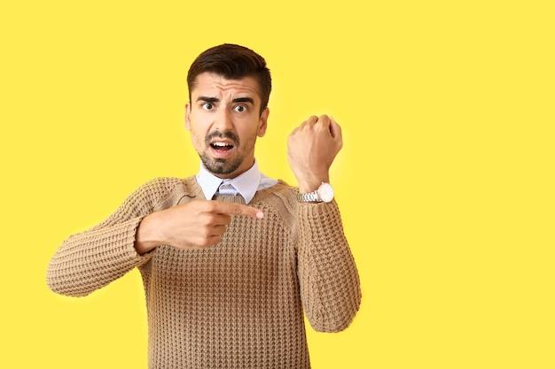 Benadrukt man wijzend op zijn polshorloge op kleur achtergrond