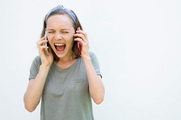 Benadrukt opgewonden jonge vrouw met gesloten ogen schreeuwen